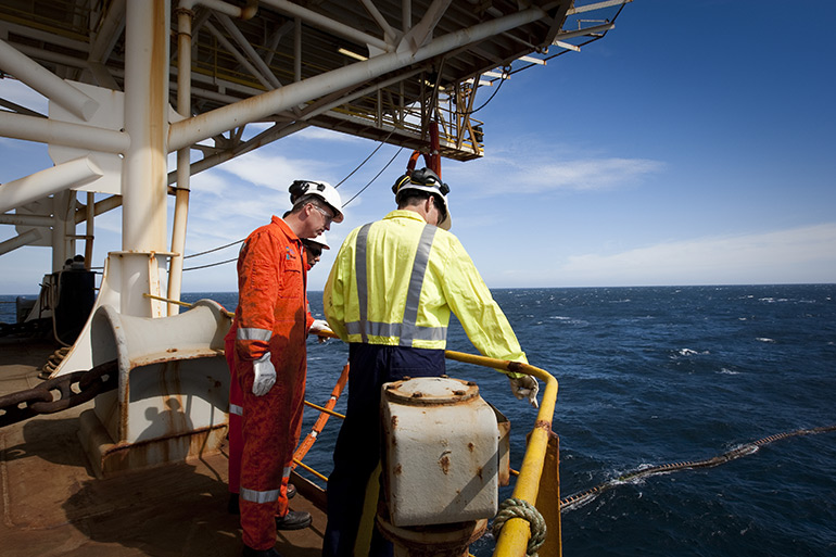 Technicians and engineers stand on the edge of an oil ship observing an oil field